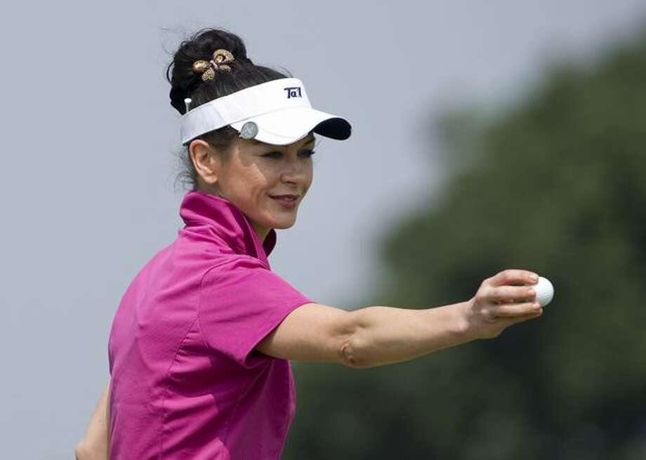 Actress Catherine Zeta-Jones holds a ball on the 14th green during day three of the Mission Hills Start Trophy tournament at Mission Hills Resort in Haikou, China. Photo: Getty Images / Getty Images