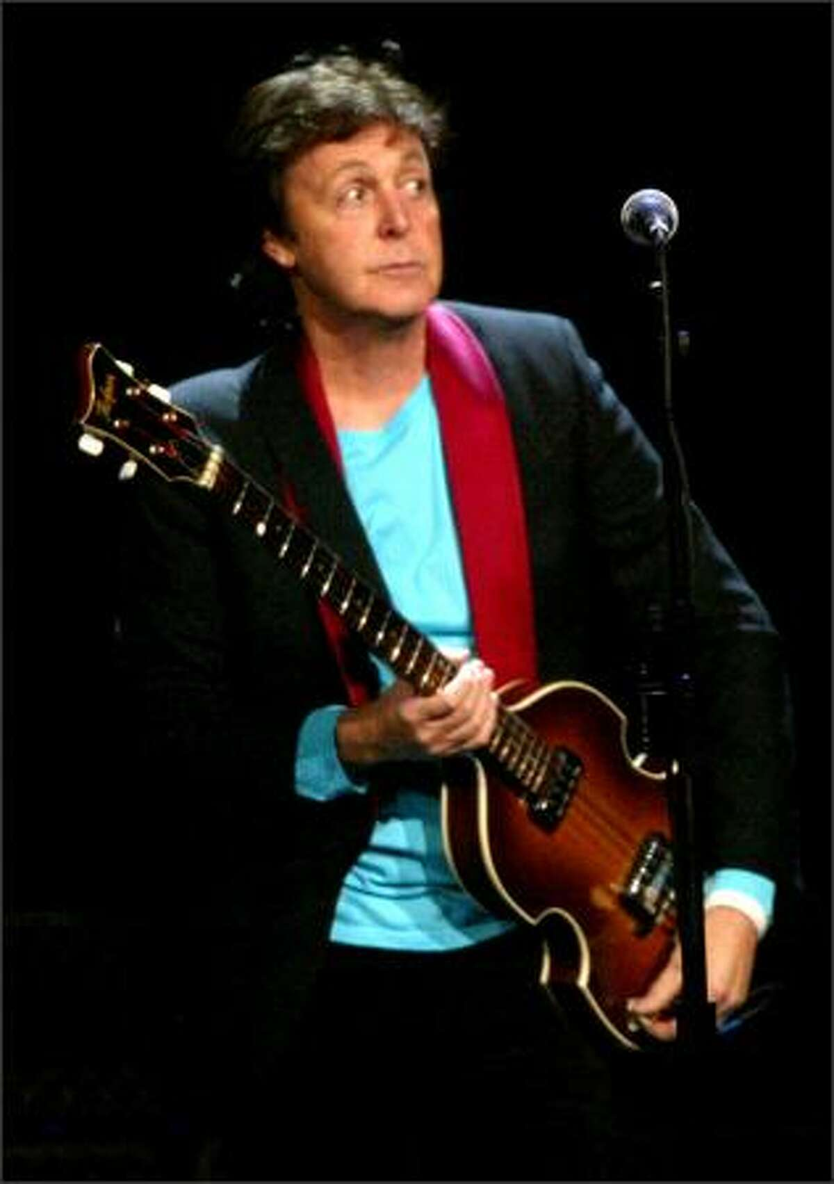Paul McCartney adjusts his bass as he and his band perform.
