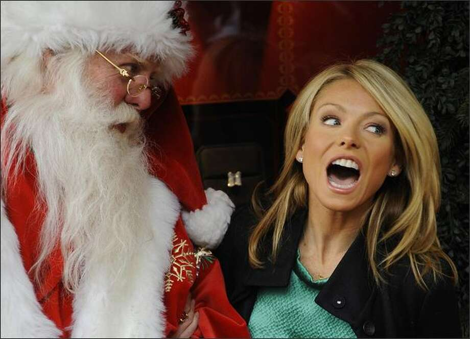 Actress and television talk show host Kelly Ripa (R) poses with Santa Claus as she unveils French luxury shop Cartier's Christmas windows along Fifth Avenue in New York. Photo: Getty Images / Getty Images