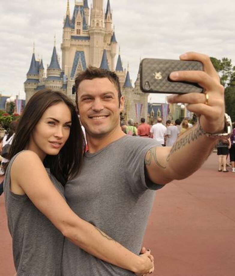 Actor Brian Austin Green (right) and his wife, actress/model Megan Fox (left), take a souvenir photo in the Magic Kingdom in Lake Buena Vista, Florida. Photo: Getty Images / Getty Images