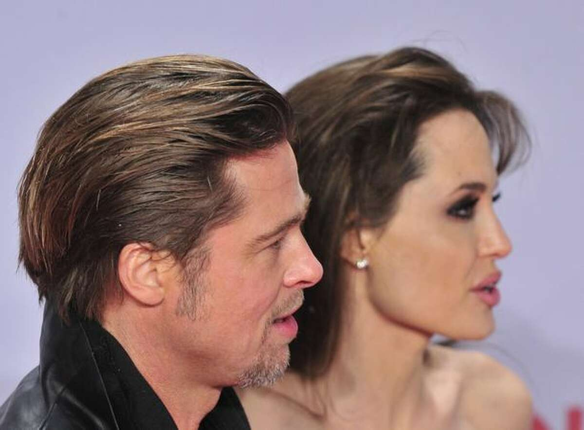 US actor Brad Pitt and actress Angelina Jolie pose for photographers as they arrive for the European premiere of the film
