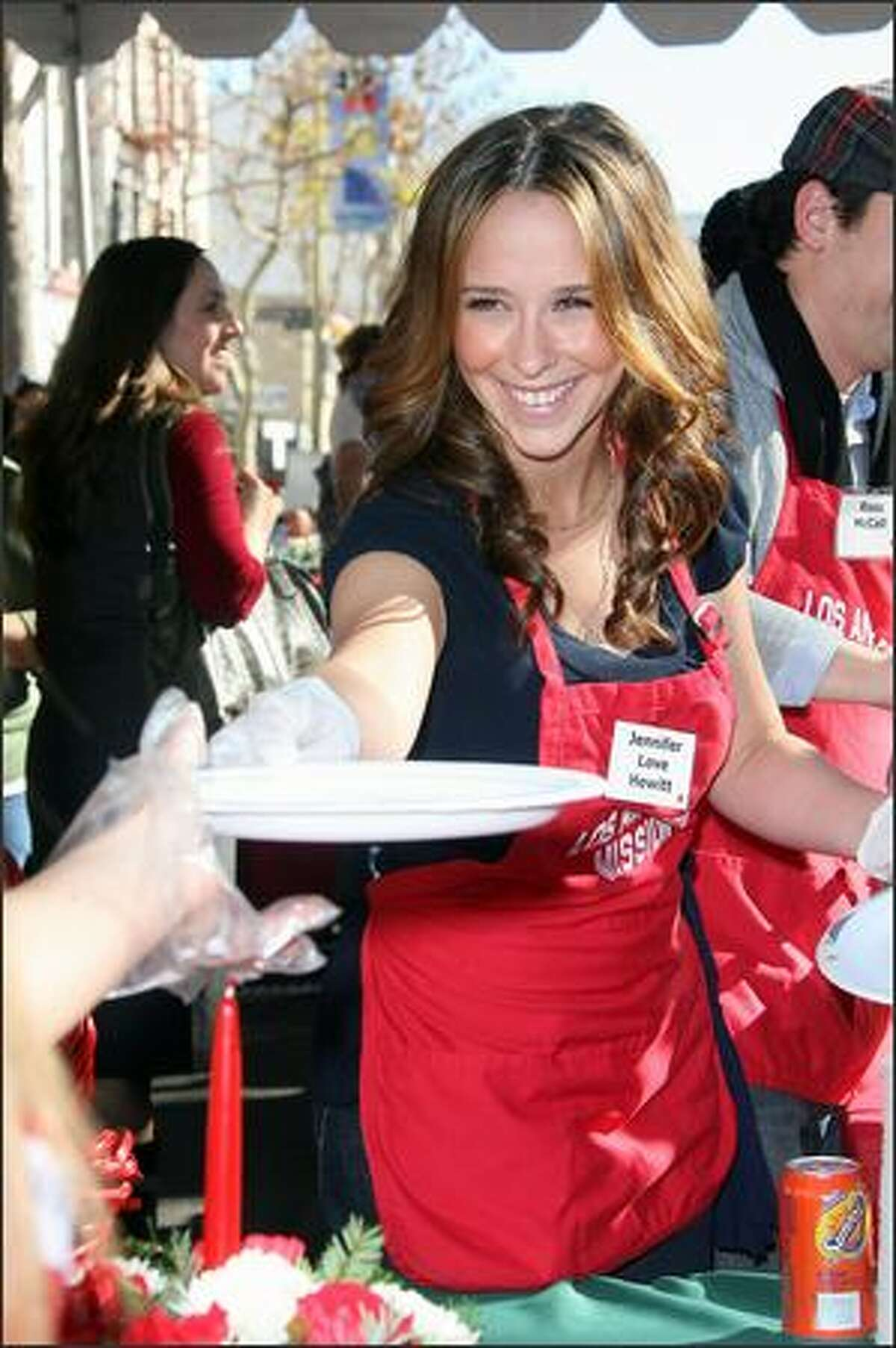 Actress Jennifer Love Herwitt serves Christmas meals to the homeless on Christmas Eve at the L.A. Mission in downtown Los Angeles, California.