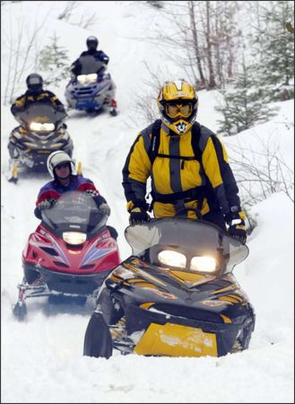Curtis Anderson kneels on his snowmobile seat to better balance his machine on bumpy terrain while riding with a caravan of Cascade Driftskippers members to gather Christmas trees near Easton.