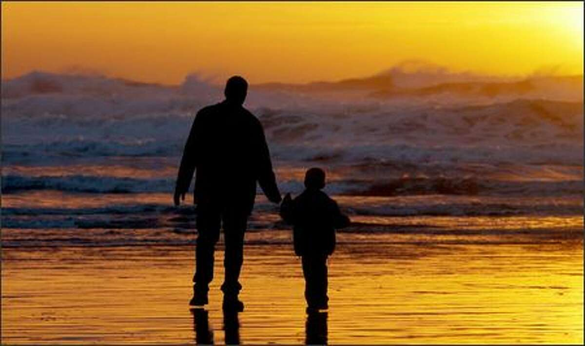 Tim McCurry with his three-year-old son, Cameron, view a Pacific Ocean storm on the beach at Heceta Head on the central coast of Oregon. McCurry and his family were visiting relatives in Eugene.