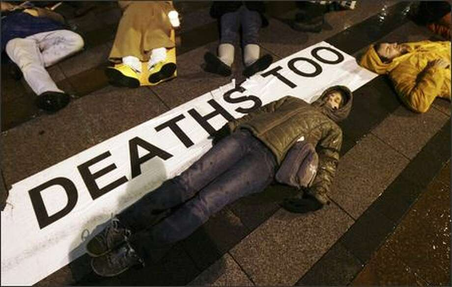 "Carrie Hathorn, center, and Josh Farris, right, both of Seattle, lie on the ground during a ""die-in"" at Westlake Center with other Iraq war demonstrators. Photo: Andy Rogers, Seattle Post-Intelligencer / Seattle Post-Intelligencer"