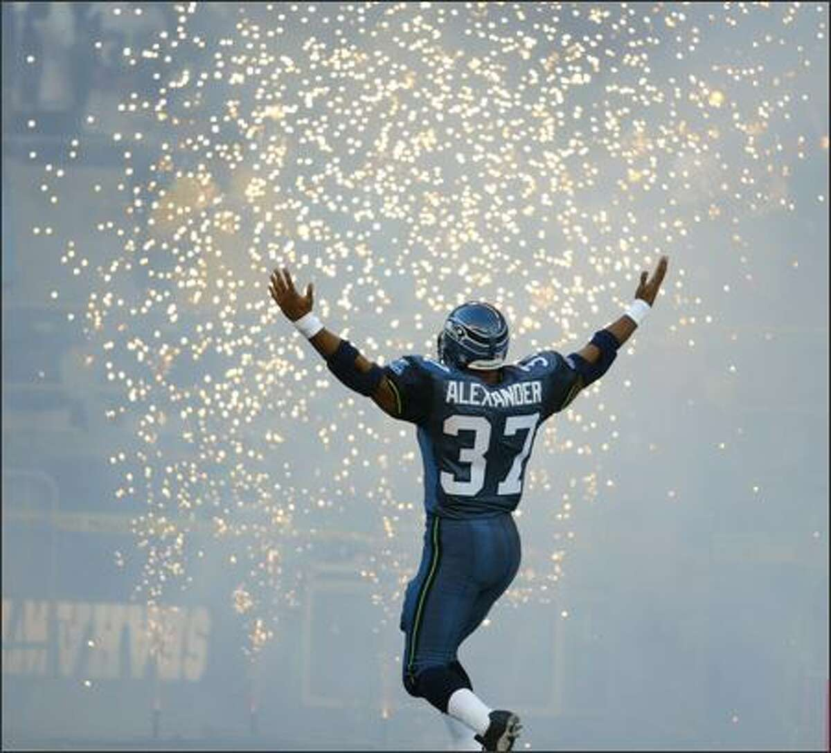 Accompanied by fireworks, Shaun Alexander encourages the crowd at Qwest Field to cheer as he is introduced before the Seahawks' game against the Atlanta Falcons. The Seahawks won 28-26.
