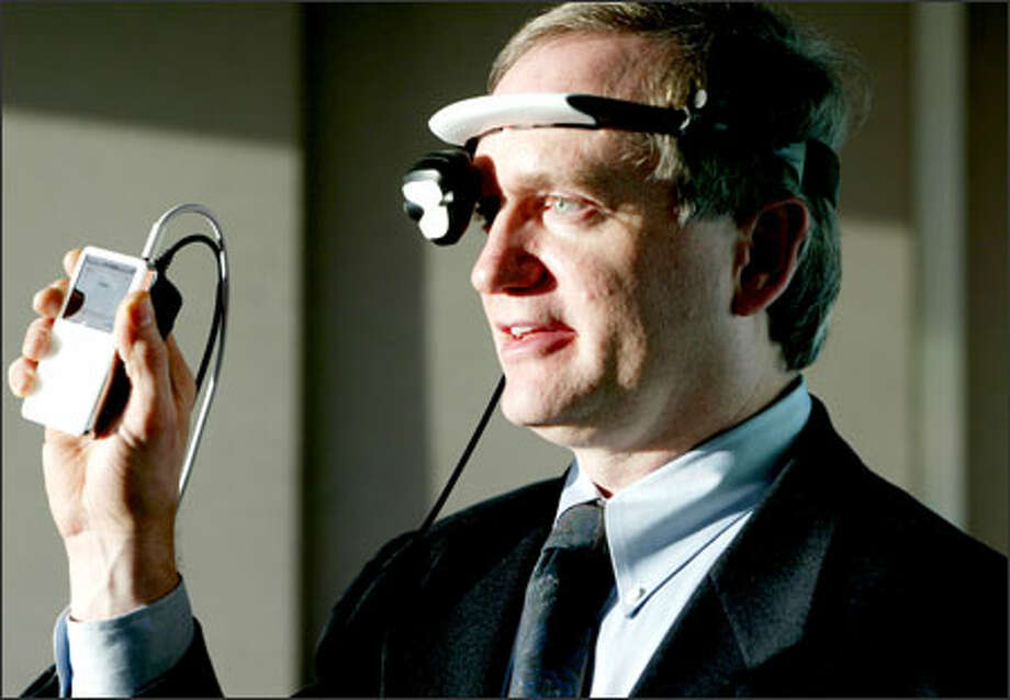"Gary Jones, president and CEO of eMagin Corp. of Bellevue, demonstrates his company's new wearable display for video iPods. Using the EyeBud headset is akin to watching a 105-inch display from 12 feet away. ""Suddenly you've got this big-screen, movie-screen, home-theater experience wherever you are,"" he says. Photo: Paul Joseph Brown, Seattle Post-Intelligencer / Seattle Post-Intelligencer"