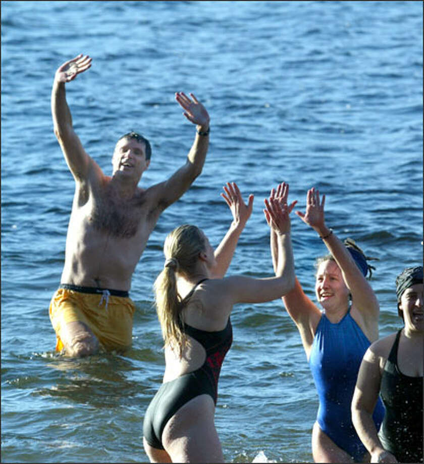 "Students and faculty, including Scott Murdoch, left, and Eliza Carlson, right, take a dip in Lake Washington to kick off the start of winter quarter at Bastyr University in Kenmore. The ""Splash and Dash,"" which attracted about 25 people, was started seven years ago by Murdoch and a friend. At noon, participants run down the hills of Saint Edward State Park, then plunge right into the lake's chilly waters. Photo: Karen Ducey, Seattle Post-Intelligencer / Seattle Post-Intelligencer"