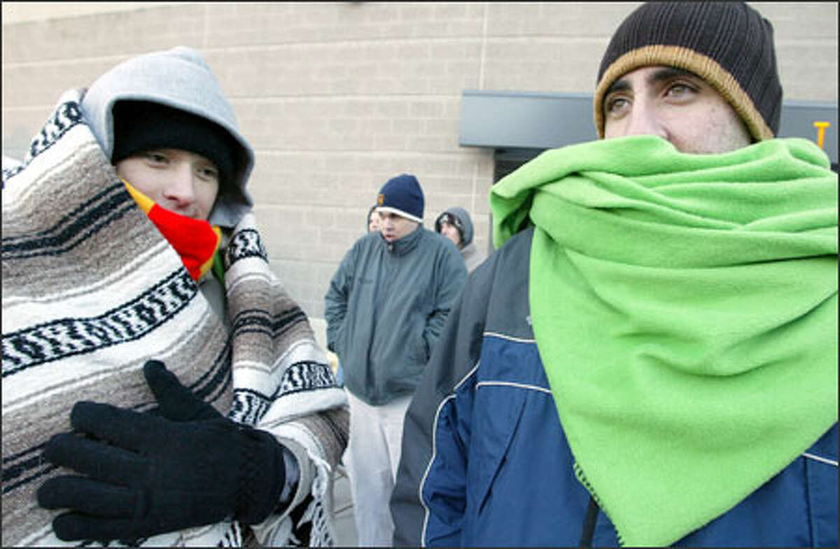 Bundled nearly beyond recognition, friends Phil Novak of Kirkland, left, and Joseph Shmait of Redmond waited in line at Qwest Field beginning at 4 a.m. The ticket booth, selling seats for the Seahawks' playoff game Saturday, didn't open until 10 a.m. It's going to stay cold for the next few days, with snow forecast for later this week.