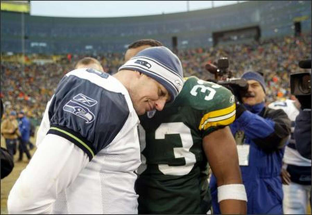 Seahawks quarterback Matt Hasselbeck gets consoled by former teammate William Henderson (33) after giving up the game-winning interception in overtime.