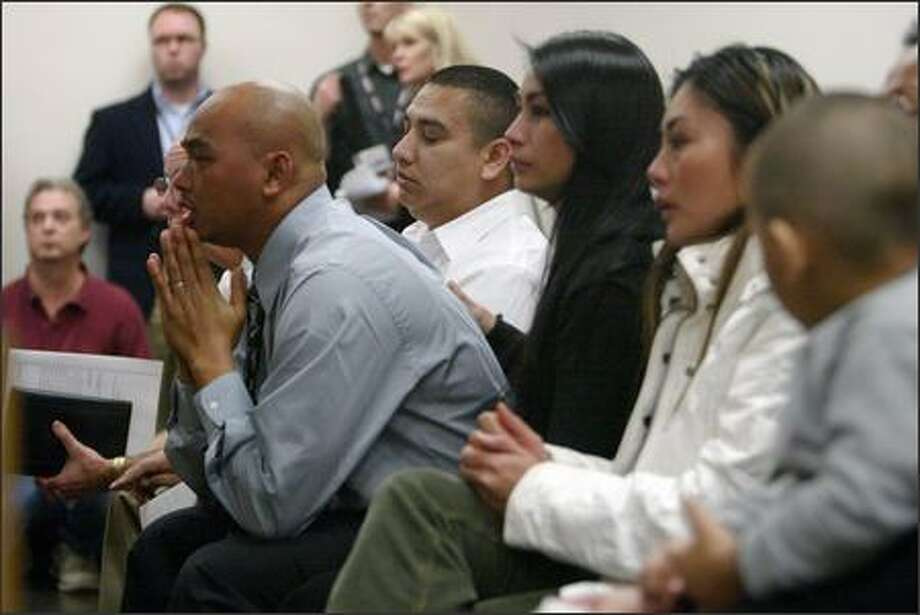 Rith Kok, on far left holding hand to face, listens during the arraignment of Douglas Chanthabouly in Tacoma on Thursday.  Chanthabouly faces first-degree murder for killing Kok's 17-year-old brother, Samnang Kok, at Foss High School on Wednesday. Photo: Gilbert W. Arias, Seattle Post-Intelligencer / Seattle Post-Intelligencer