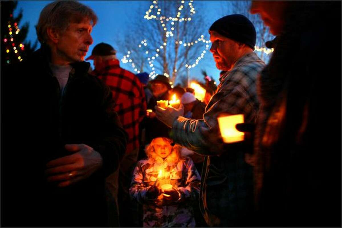 Six year old Elliott, center, and her dad John, right, gather with other local residents along Tolt Avenue in Carnation during a memorial vigil. The vigil was in response to the Christmas Eve killing of six in the small east King County town.