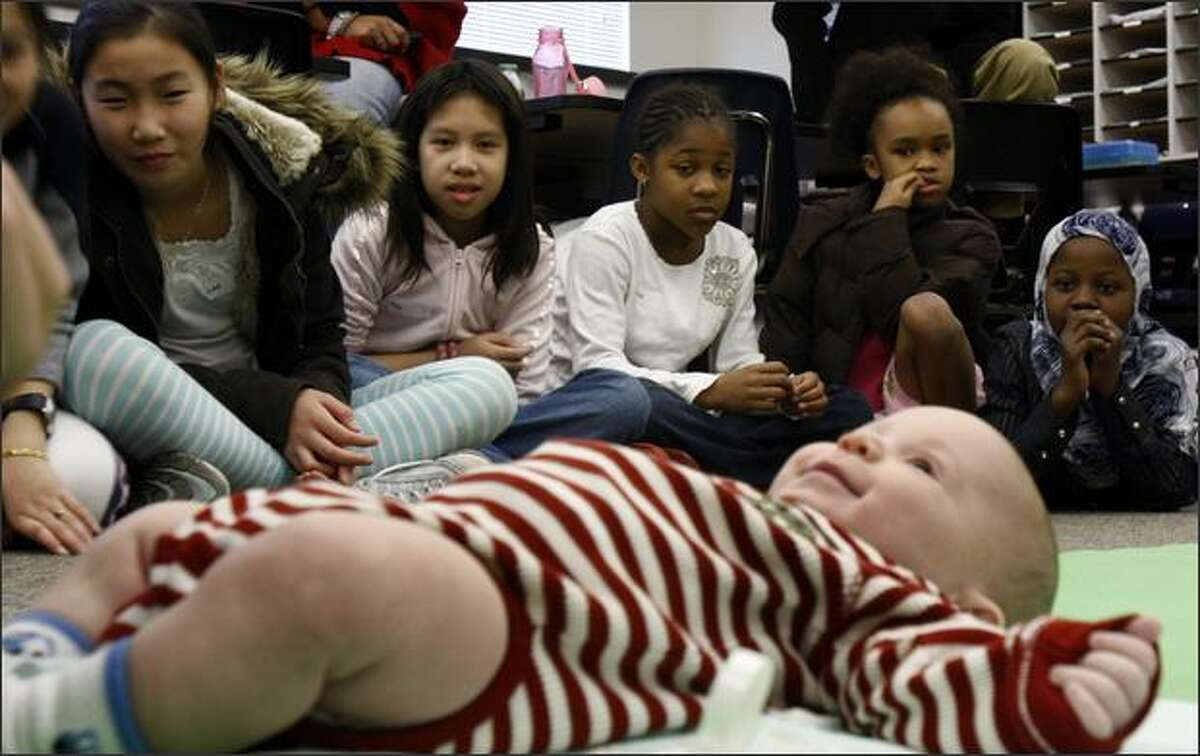Linh Duong,left, YongQian Chen, Jasmine Scott, Loni Stubblefield and Khadijo Adan observe as fourth-month-old Matthew Moretsky has a diaper changed by his father Michael in Kimberly Rothschild's fourth and fifth grade classroom. The infant visit to the classroom is part of a the