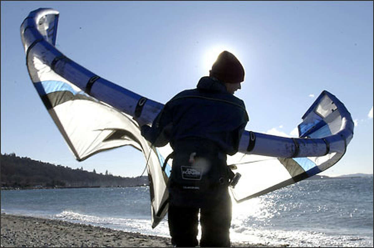 Terrance Towe carries his kite along the beach at Golden Gardens after a short kite boarding session on a windy Sunday. It was a frigid day: The temperature got up to just 27 at Sea-Tac Airport.