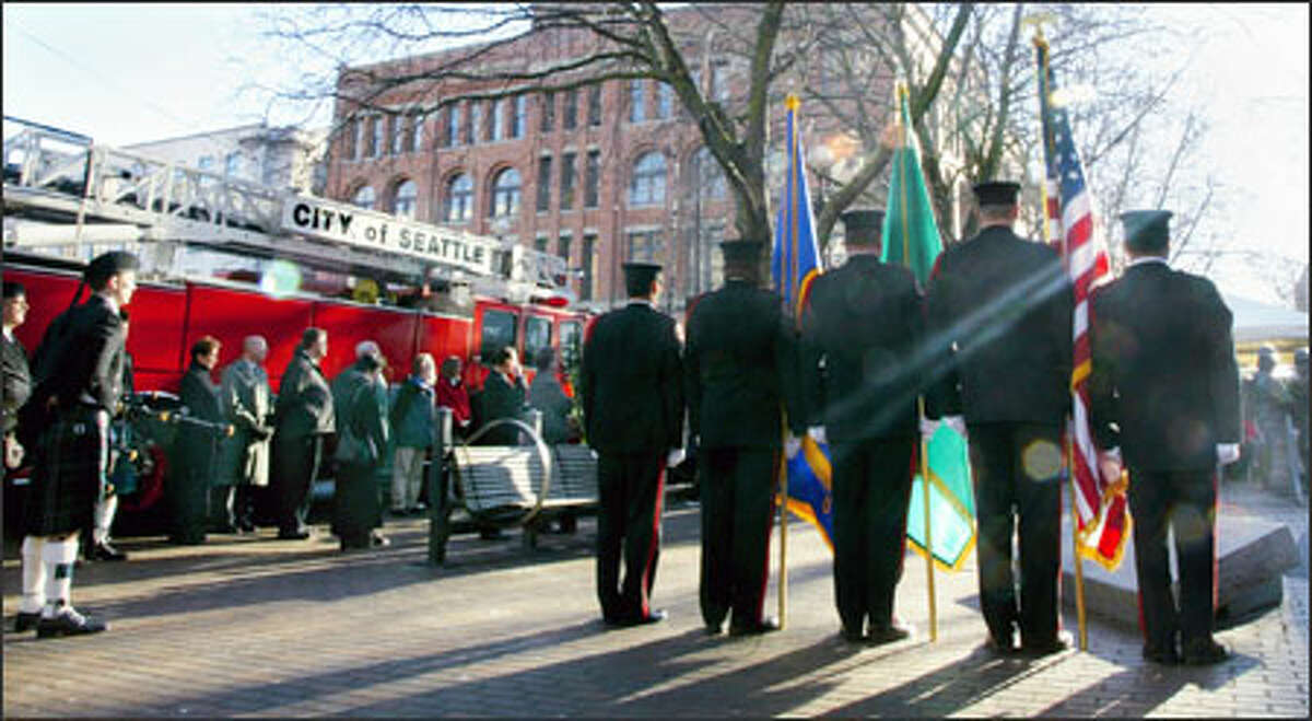 At the Fallen Firefighter Memorial in Occidental Park, an honor guard stands at attention during a ceremony to remember four Seattle firefighters who died in the Pang warehouse fire 10 years ago.
