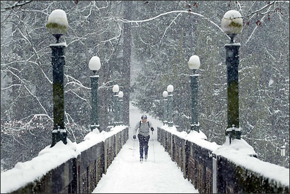 Under heavy snowfall, Paul Milan cross country skis on a footbridge spanning Lake Washington Boulevard in Montlake. Milan skied from his home on Capitol Hill. More than 4 inches of snow fell on Seattle.
