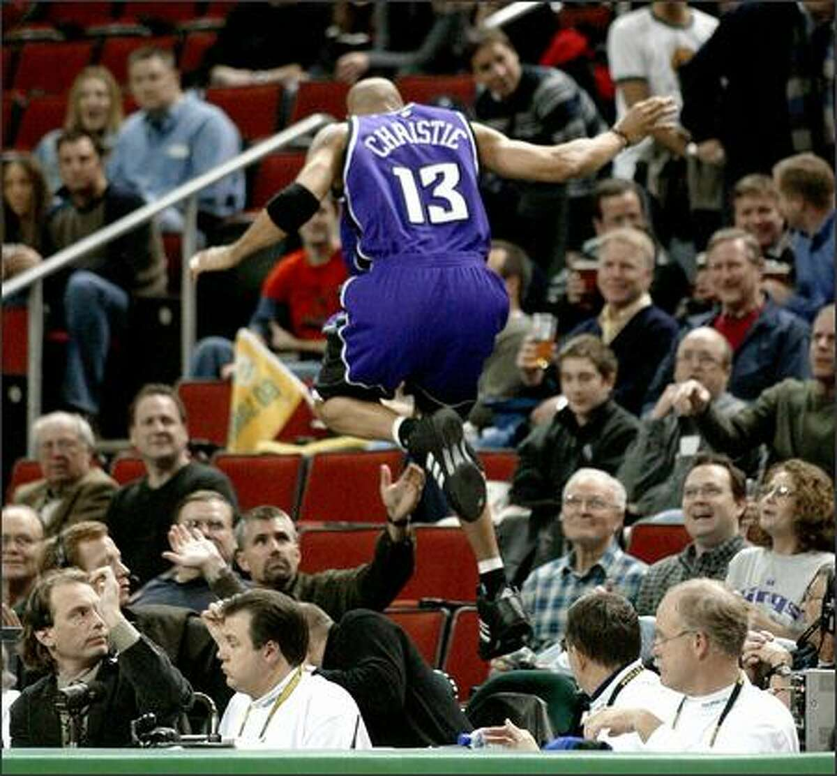 Kings guard Doug Christie, a former Rainier Beach High School standout and Sonics draft pick, leaps into the stand after chasing a loose ball.