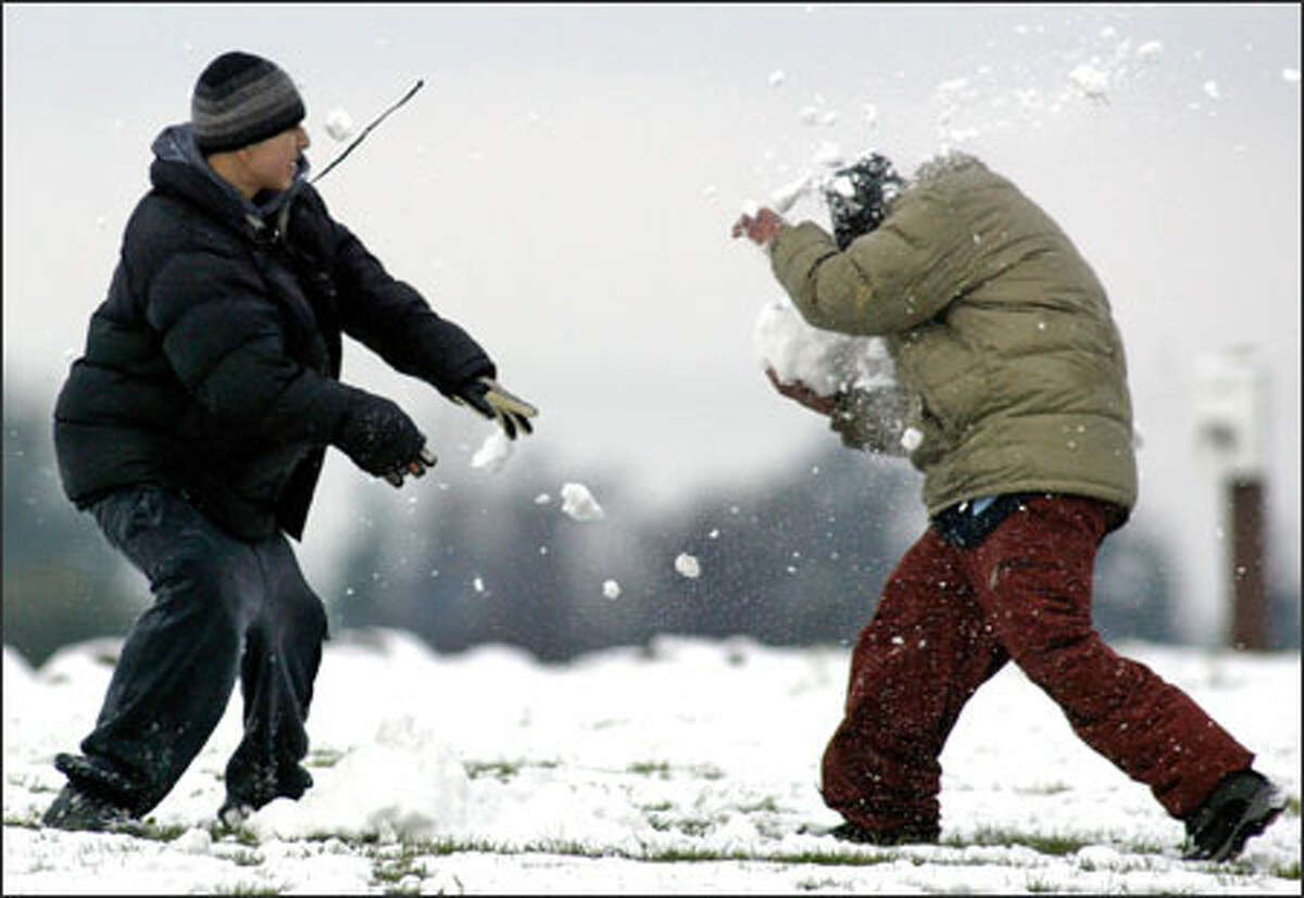 George Munoz, left, hits Luis Reyes with a snowball as they enjoy the snow while it lasted in White Center's Westcrest Park.