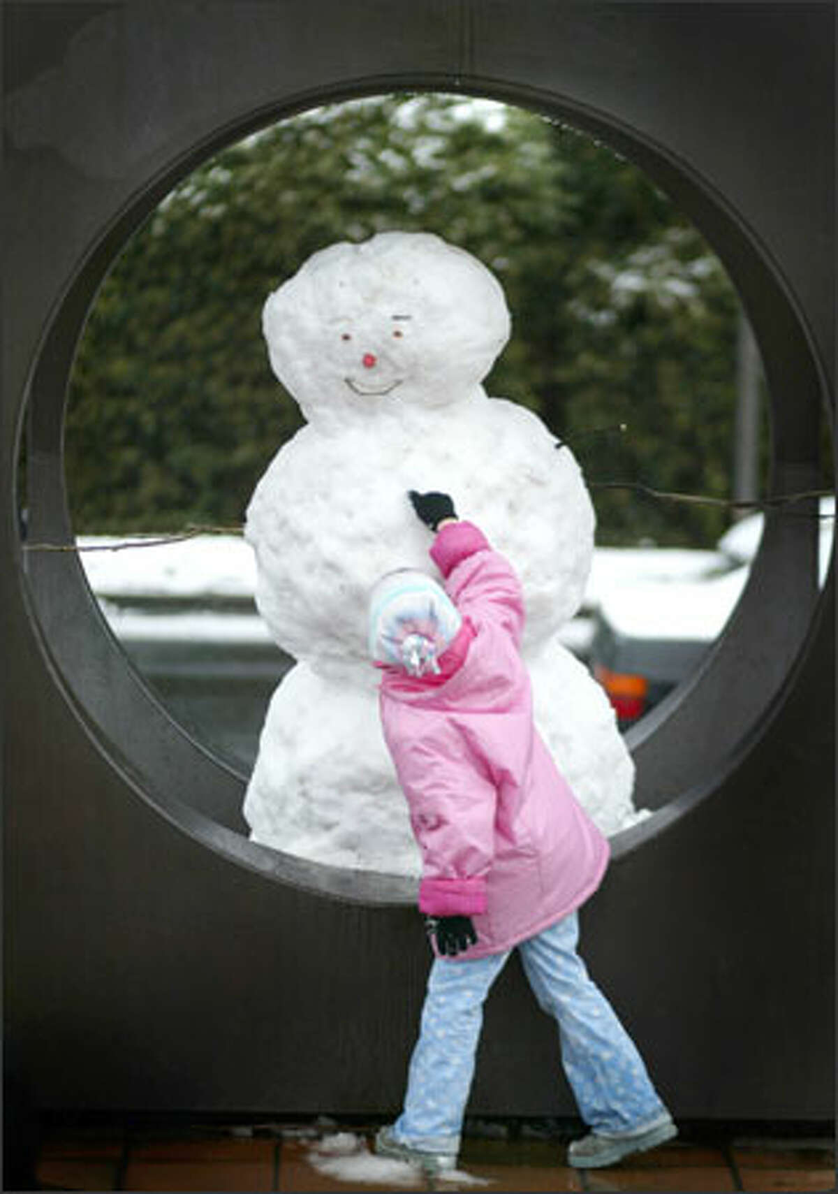 Sanuye Ford, 6, checks out the button of a snowman built inside the sculpture at Kerry Park on Queen Anne Hill. Seattle received a dusting of snow, with more of it falling north of downtown, early in the day. It brought out residents ready to play as well as city workers ready to plow and sand. The snow quickly melted.