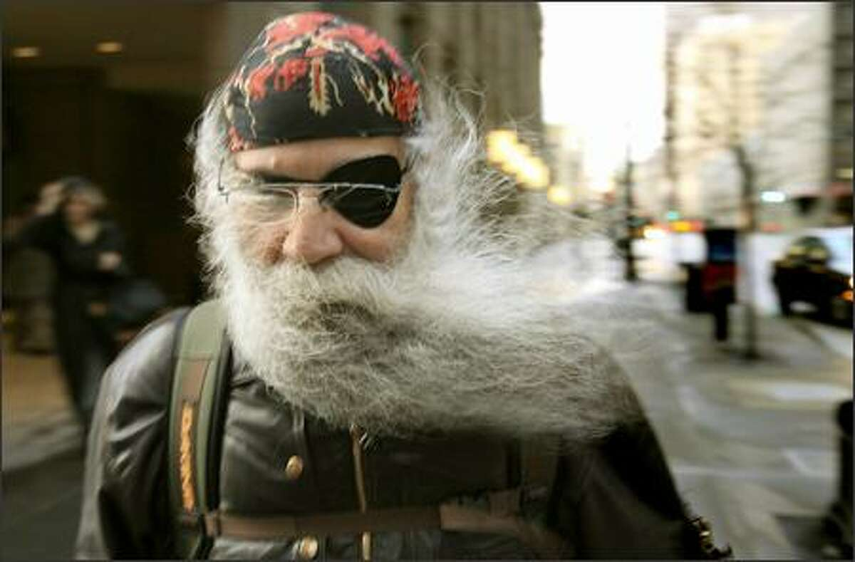 A strong gust of wind sends Frank Zamfino's beard flying as he walks along Third Avenue in downtown Seattle.