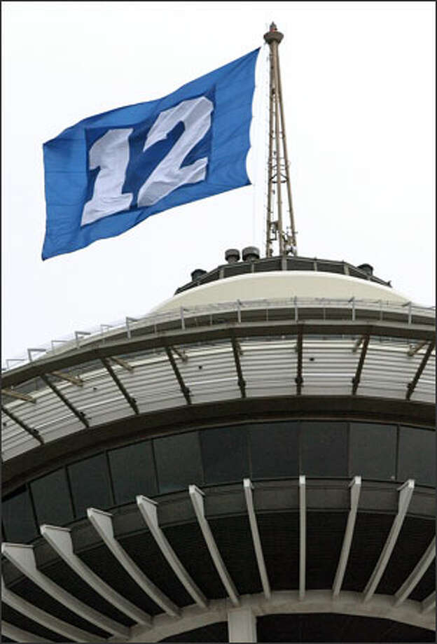 "Battling 35mph winds atop the Space Needle, mountain climber Ed Viesturs hoists a Seahawks ""12th Man"" flag over Seattle Tuesday. The flag, which represents fans of the record-setting football team, will fly during the upcoming Seahawks playoff run. Photo: Mike Urban, Seattle Post-Intelligencer / Seattle Post-Intelligencer"