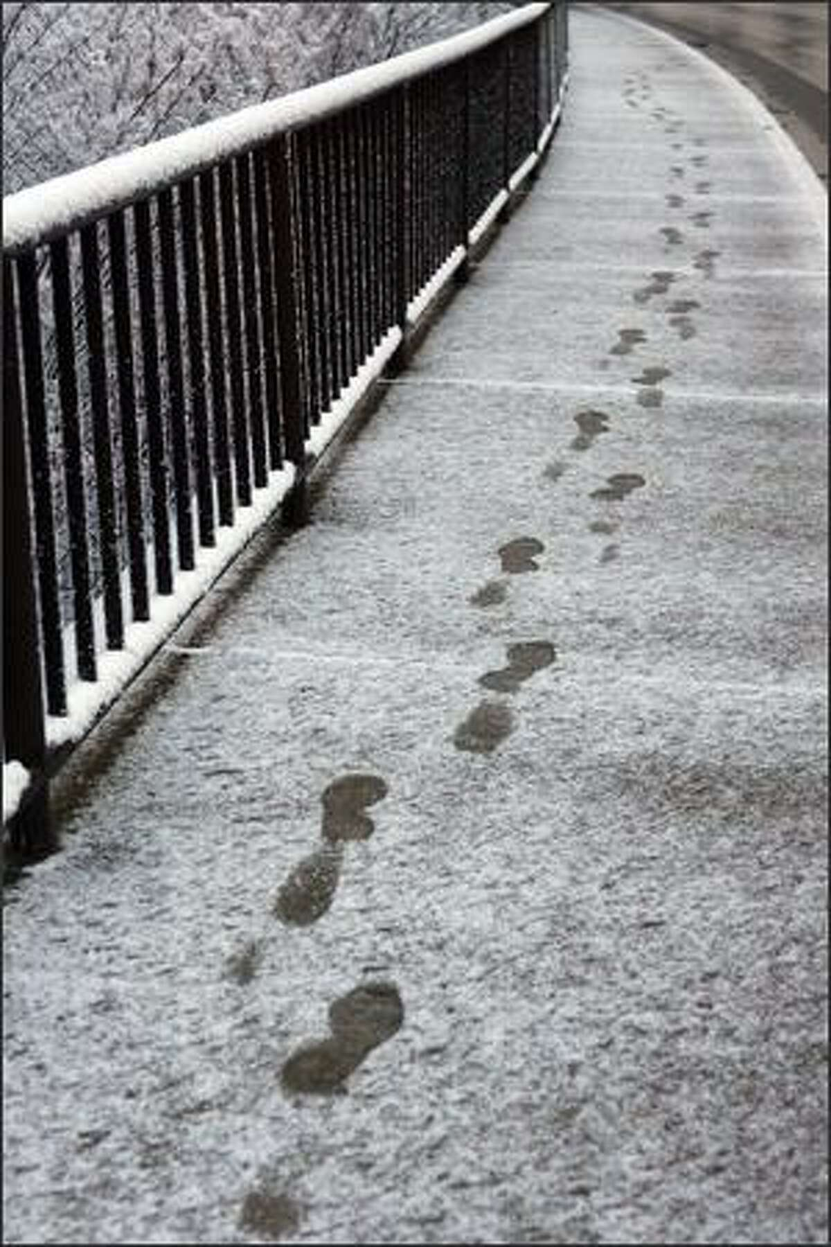 Footprints in snow on a sidewalk along U.S. Highway 527 in Snohomish County near 128th Street S.W. Wednesday morning.