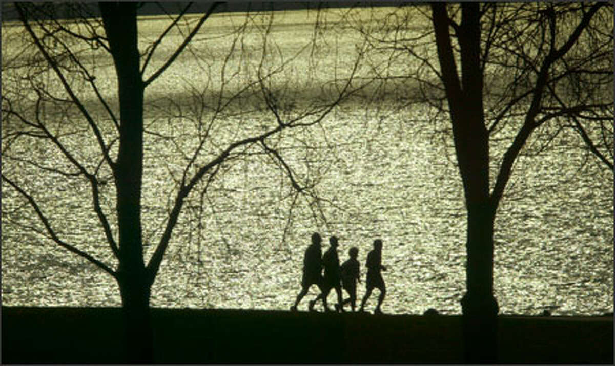 The sun reflecting off Elliott Bay silhouettes four lunch-hour joggers in chilly Myrtle Edwards Park.