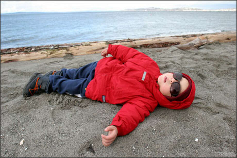 Sure, Seattle's break from the rain didn't last long Wednesday, but it was enough to get Ian Suarez, 3, out to the beach at Alki with parents Erika Rodriguez and Jaime Suarez to fly a kite. Here Ian borrows his mom's sunglasses to take a rest. Photo: Meryl Schenker, Seattle Post-Intelligencer / Seattle Post-Intelligencer