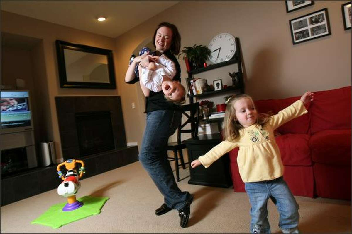 Karen Barker plays with her daughters, Katie, 2 (right) and Megan, 12 months, at their home in Woodinville, WA. She used a parent coach to help her manage all her responsibilities.