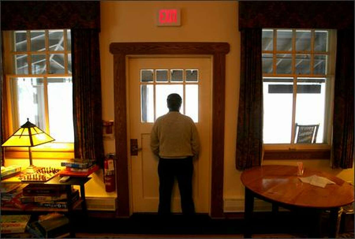 National Park Inn manager Mike Bradford looks out the back window as he waits for his guests to arrive. On this day only two rooms are rented, when normally at this time of year about 22 rooms are occupied. With the main road to Mount Rainier gone, visiting the park is now a completely different experience.