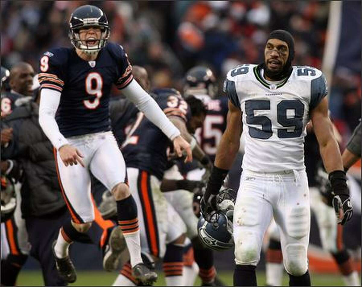 Chicago Bears kicker Robbie Gould (9), who just kicked the winning field goal in overtime, literally floats off the field as Seattle Seahawks linebacker Julian Peterson (59) looks on stunned.