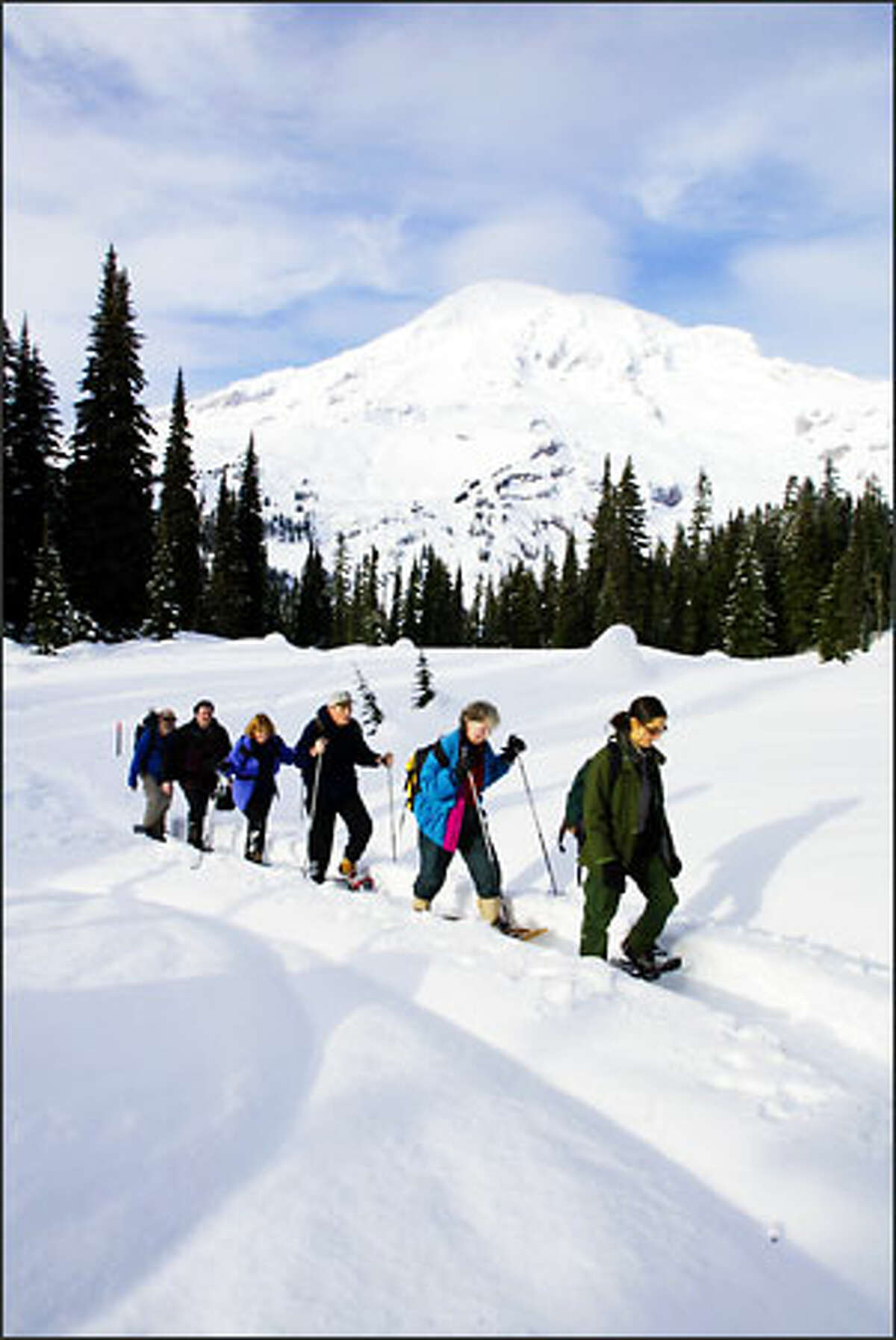 With Mount Rainier's summit looking in the background, ranger Dana Ostfeld leads a two-hour snowshoe walk from Paradise.