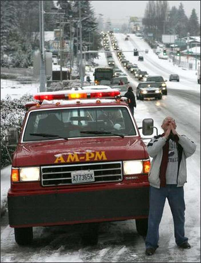 Jack Dragovich, who got stuck at 6:30 a.m., gives thanks to the powers above after Mike Gilbert of AM PM Towing finishes hooking up his truck. Gilbert had told him that he was ready to tow the truck to Dragovich's home. It was 9 a.m. Photo: Grant M. Haller, Seattle Post-Intelligencer / Seattle Post-Intelligencer