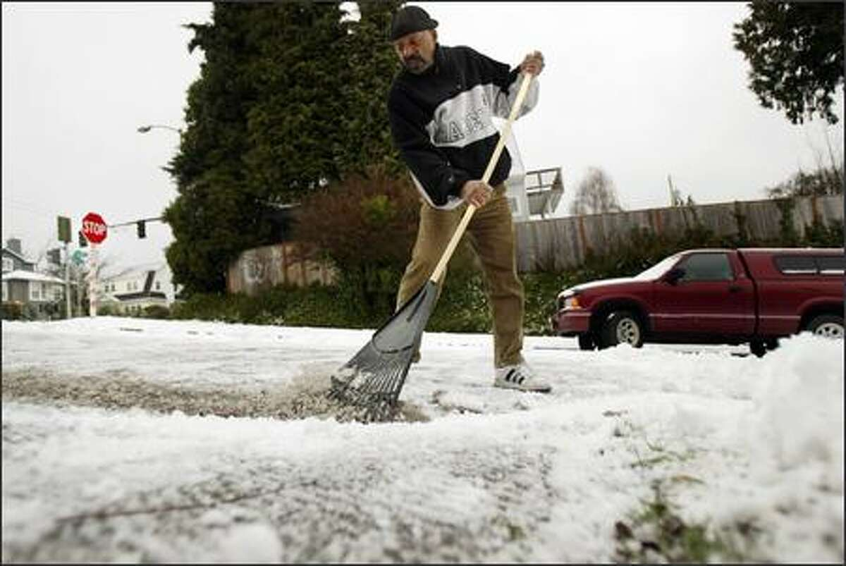 Perry Harper rakes the snow from the street in front of his home on a steep section of East Aloha Street.
