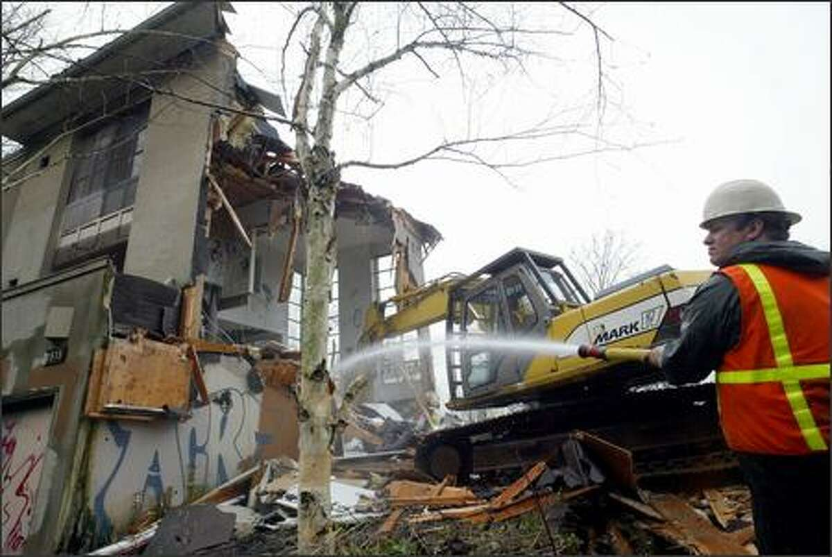 A worker for Gaston Brothers Excavation hoses the wreckage from the last of three townhouses being torn down at 1515 Lakeview Blvd. E. in Seattle yesterday.