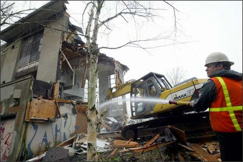 A worker for Gaston Brothers Excavation hoses the wreckage from the last of three townhouses being torn down at 1515 Lakeview Blvd. E. in Seattle yesterday. Photo: Dan DeLong, Seattle Post-Intelligencer / Seattle Post-Intelligencer