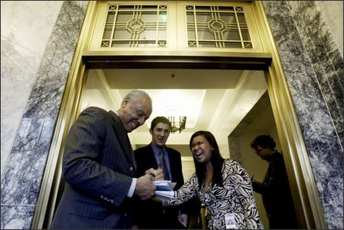 Lenny Wilkins, vice chairman of the Professional Basketball Club for the Seattle Supersonics, signs an autograph for Senate interns Brad Sherman and Kristi Noceda following a presentation to the Washington State Senate Ways and Means Committee during a hearing in Olympia.
