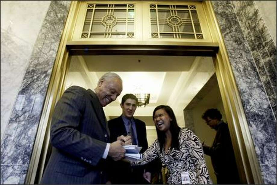 Lenny Wilkins, vice chairman of the Professional Basketball Club for the Seattle Supersonics, signs an autograph for Senate interns Brad Sherman and Kristi Noceda following a presentation to the Washington State Senate Ways and Means Committee during a hearing in Olympia. Photo: Andy Rogers, Seattle Post-Intelligencer / Seattle Post-Intelligencer