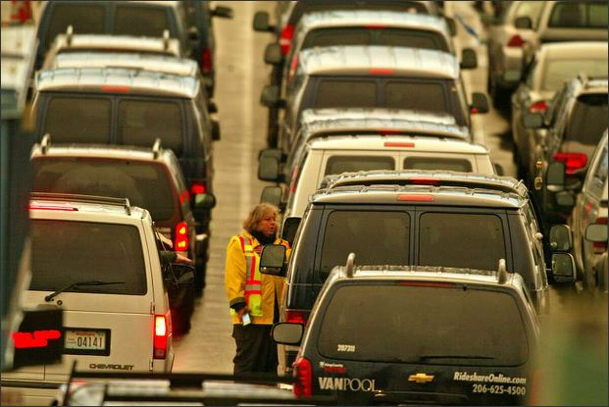 Ticket taker Chris Settles talks with a van pool driver in a long line of commuter vans waiting for the 5 p.m. ferry Issaquah at the Fauntleroy ferry dock.