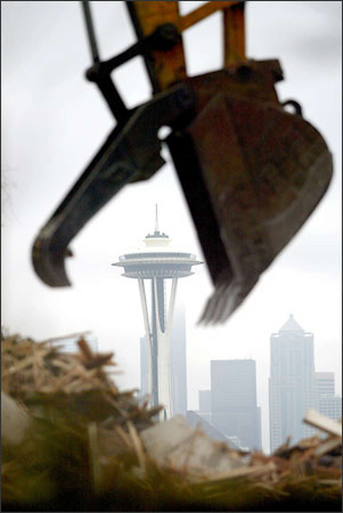 The jaws of a backhoe look as if they're about to devour the Space Needle as the operator works a pile of debris during demolition of a house on Queen Anne. The house at 222 W. Highland Drive sat across from Kerry Park Viewpoint and was built in 1914 for the J.C. Black family and designed by Andrew Willatsen, a protege of architect Frank Lloyd Wright. The house was sold last year and a permit was issued to demolish the house and garage to make room for construction of a single-family residence.