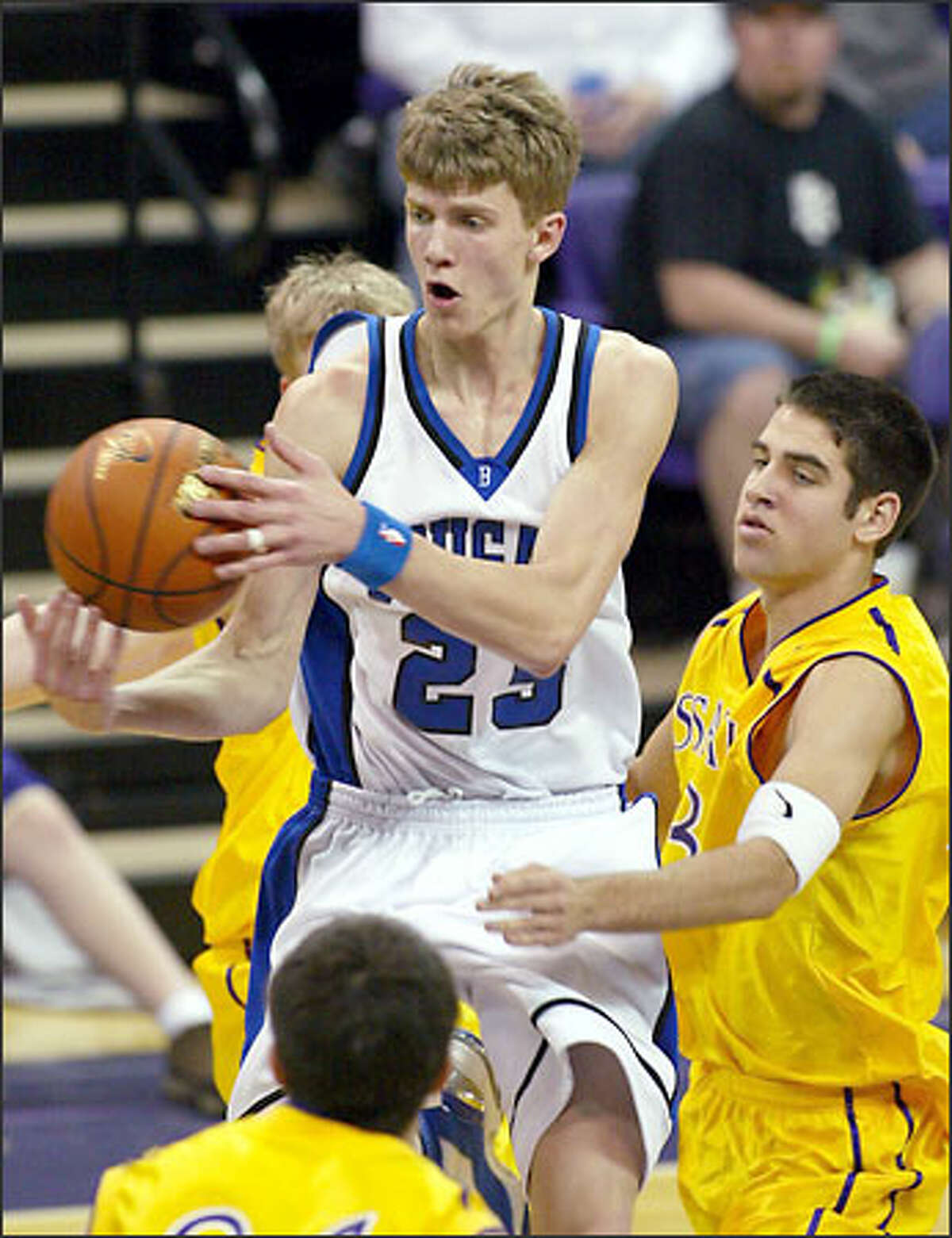 Bothell's Micah Downs, a junior transfer who finished with 16 points, 12 rebounds, four assists and four steals, beats Issaquah's Curtis Reynolds to the ball yesterday at Hec Edmundson Pavilion.