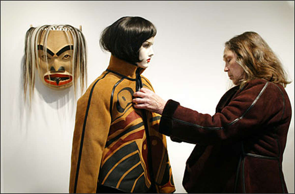 Betty David dresses a mannequin in one of her Port Madison hand-painted shearling coats in her new Pike Place Market shop.