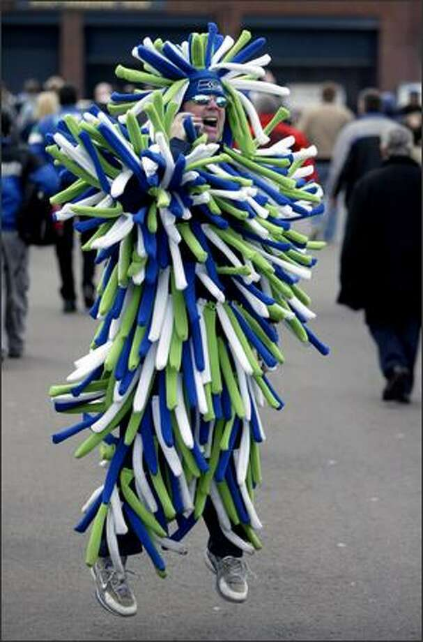 Seahawks fan Mark Williams of Puyallup jumps up in a handmade outfit as he tries to get a friend's attention prior to the NFC Championship Game between the Hawks and the Carolina Panthers.  The Seahawks won 34-14 to advance to the Super Bowl against the Pittsburgh Steelers. Photo: Mike Urban, Seattle Post-Intelligencer / Seattle Post-Intelligencer