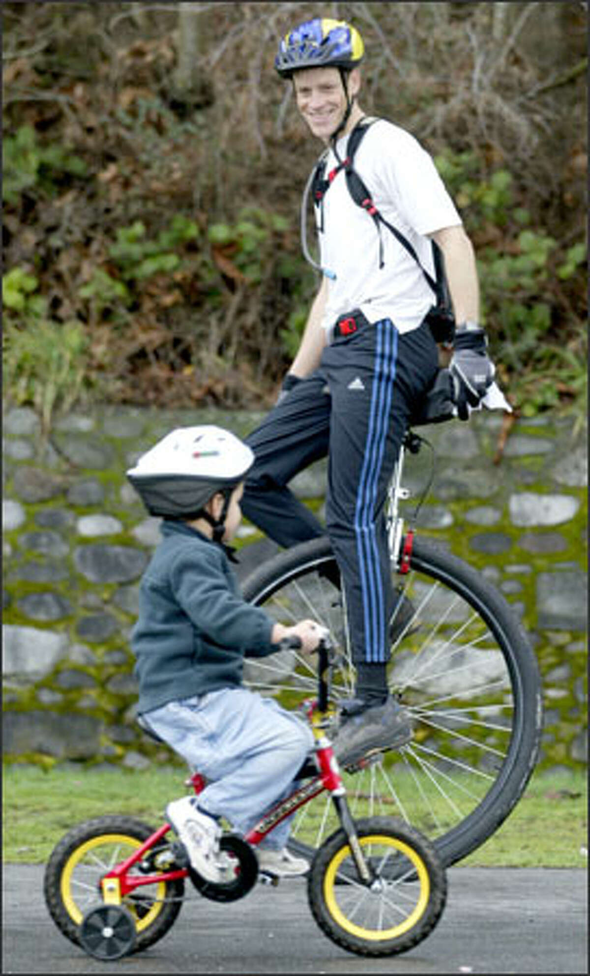 Jeff Sloan, aboard his 36-inch Coker commuting unicycle, passes 4-year-old Jackson Higuere while riding along the waterside pathway at Lincoln Park in West Seattle.