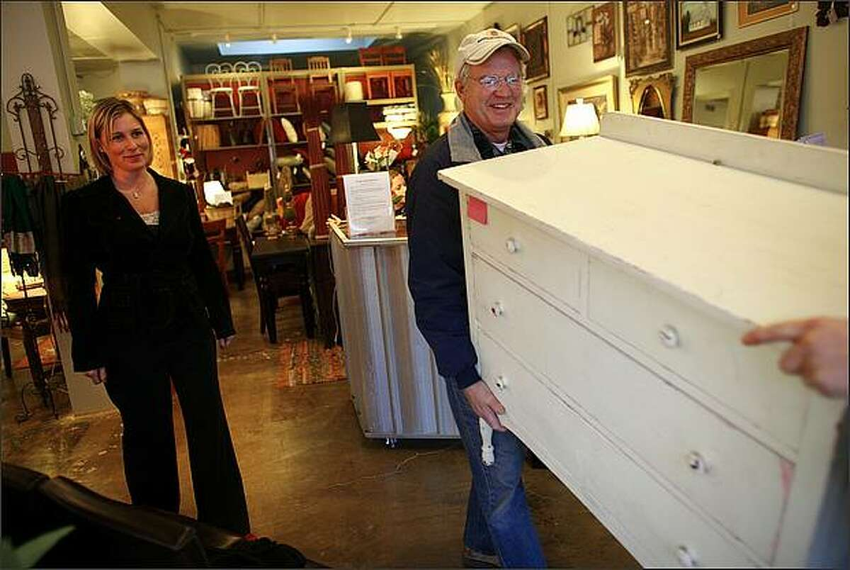 Katrina Puetz watches as customer Pat Archer and Cindy Archer, not shown, leave with an antique dresser from Puetz's retail furniture store, Furnishments in the Greenlake neighborhood.