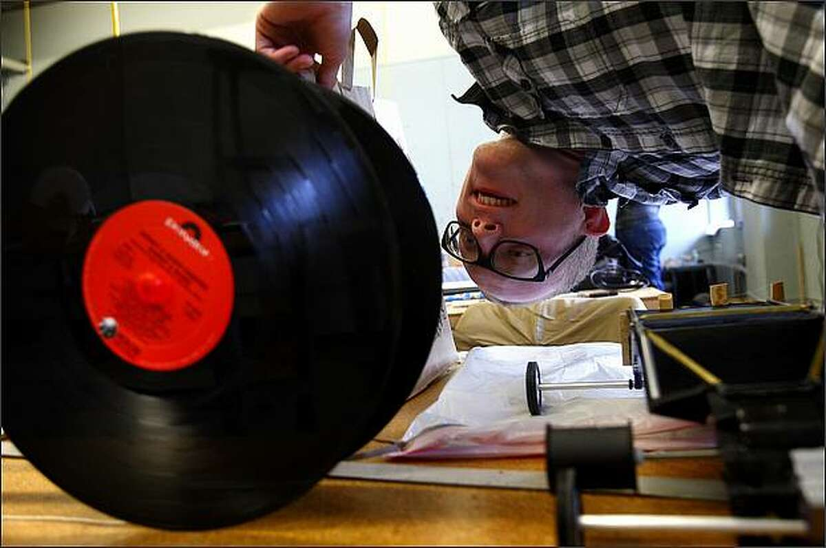 Tim Damon, a junior design studies student, reads the song list on a Billy Joel record used as a wheel on a classmate's