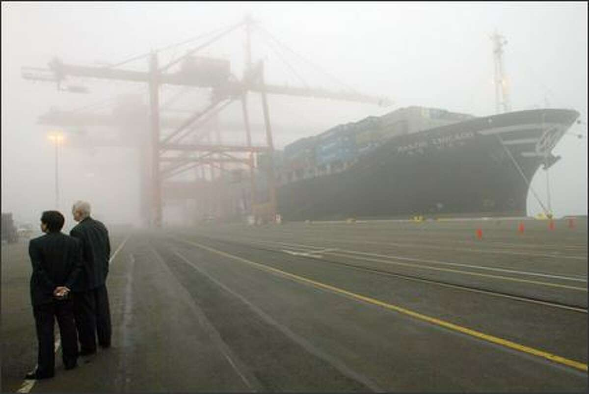J. H. Ryu, left, regional manager for the Seattle office for Hanjin Shipping, and Charlie Sheldon, managing director of the Port of Seattle's seaport division, take in the sights during a foggy-day tour of Terminal 46.