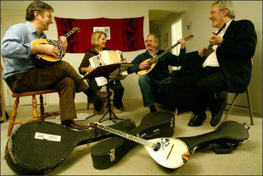 The rebetika group Christos Govetas and Pasatempos -- from left, Christos Govetas, Ruth Hunter, Hank Bradley and Steve Ramsey -- rehearse. The men play bouzoukis while Hunter plays the accordion. Photo: Paul Joseph Brown, Seattle Post-Intelligencer / Seattle Post-Intelligencer
