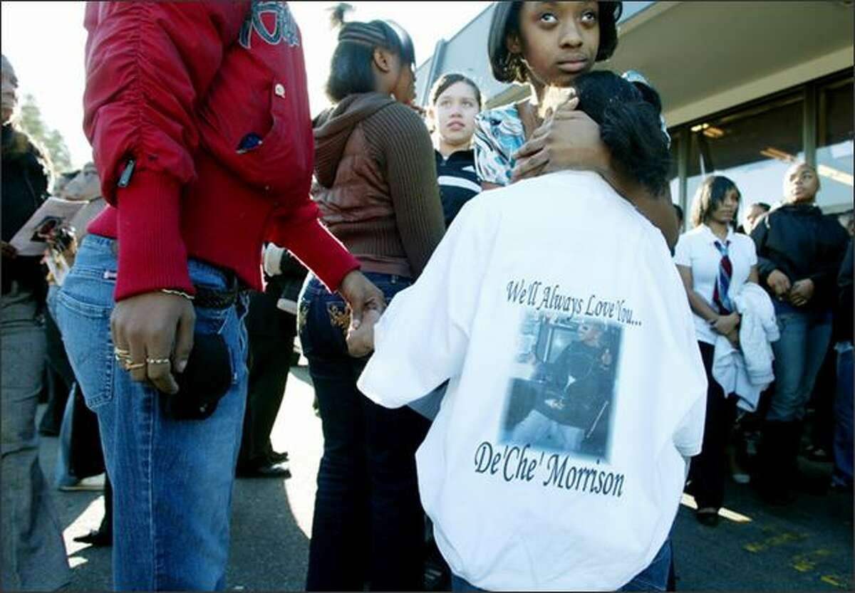Jamazia Brown, 8, wearing a shirt in honor of her cousin Deche Morrison, 14, at Morrison's funeral at the Freedom Missionary Church in West Seattle. Holding Jamazia's hand is her step-mother Jimmia Brown.