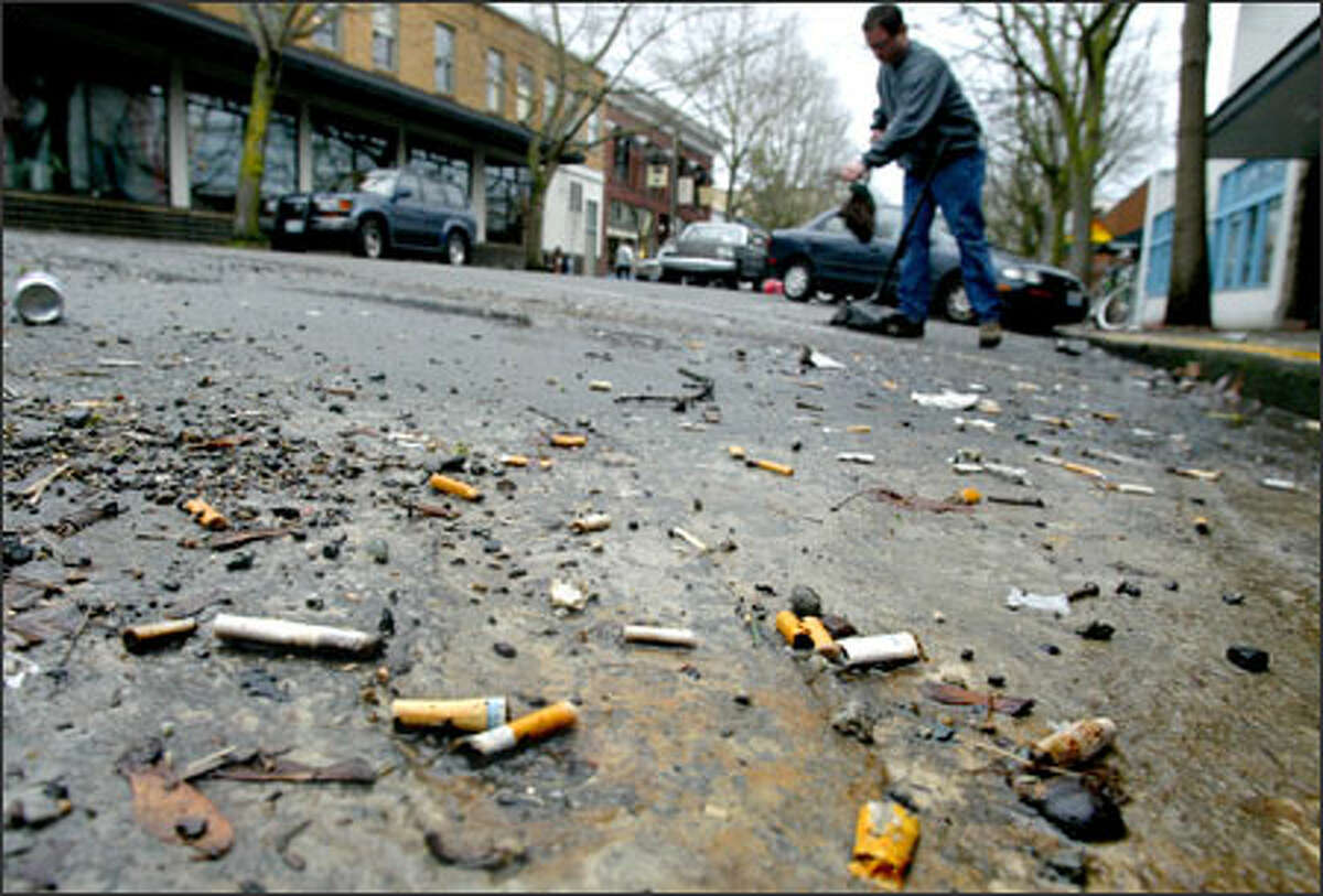 Rudy McCoy-Pantoja sweeps up cigarette butts at Ballard Avenue and Northwest Market Street in Ballard.